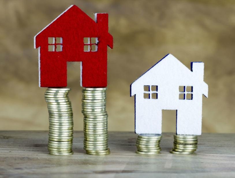 Pile de pièces et maisons miniature