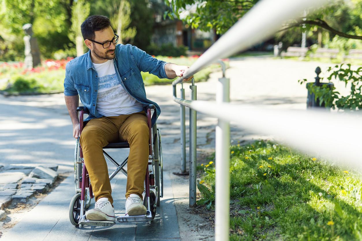 Une personne à mobilité réduite avec une rambarde